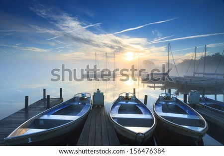 Foggy and tranquil sunrise at some boats in a small marina on a lake.  - stock photo