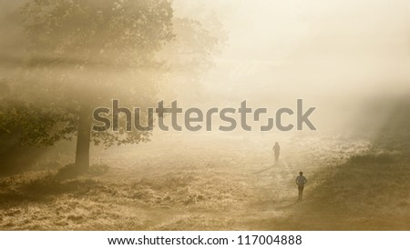 Foggy Autumn morning in Richmond Park, London with joggers running through landscape - stock photo