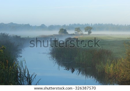 Foggy, autumn sunrise at a small stream in the Dutch countryside. Drenthe, Holland. - stock photo