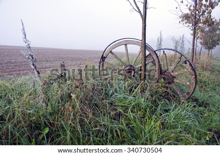 Foggy autumnal landscape with two decorative antique horse carriage wooden wheels