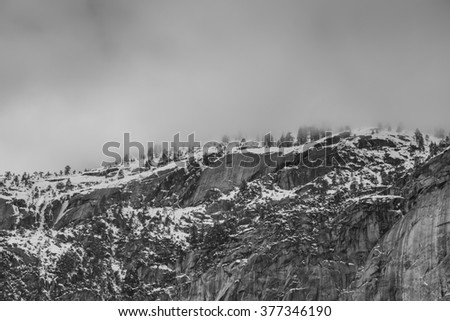 Foggy black trees and granite mountains from thunder storm at Yosemite Valley-2 - stock photo
