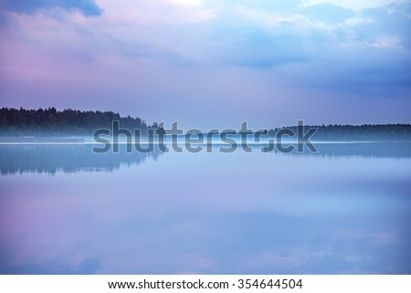 Foggy early morning sunrise on a calm mirror surfaced lake - stock photo