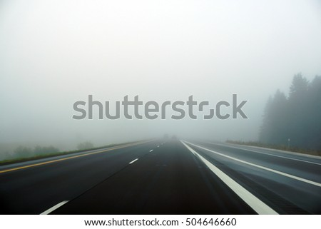 Foggy highway on cold October morning with very little traffic