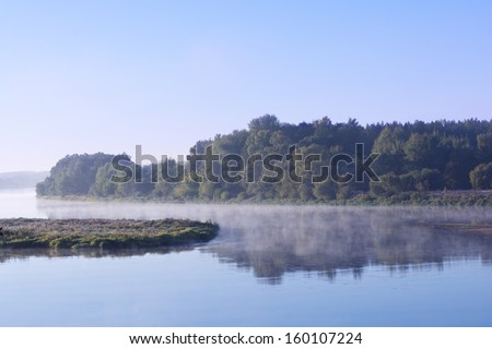 Foggy landscape with tree silhouette and reflection on water on fog at sunrise.Early summer morning on tranquil lake.Morning Lake.Misty morning on lake. Lithuania. Nemunas river - stock photo