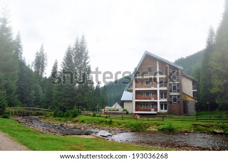 Foggy morning in the Carpathian Mountains, the cottage in the woods - stock photo