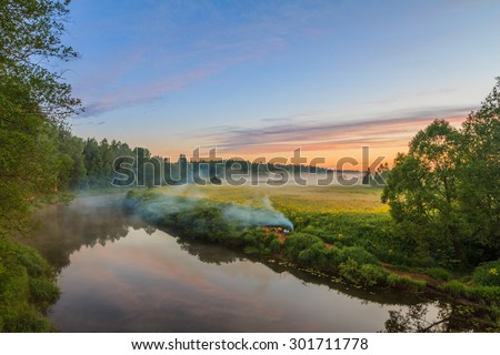 Foggy morning. Morning on the river bank. Reflection of trees in water. Fire on the river bank. Bright colourful fine clouds at sunrise. Trees in fog