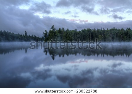 Foggy morning on  Seventh Lake in the Fulton Chain Lakes region of the Adirondack Mountains of New York - stock photo
