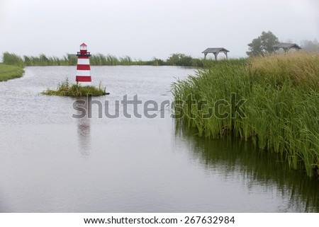 Foggy morning on the lake and small lighthouse, Maine, USA - stock photo