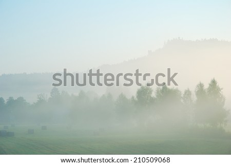 Foggy morning rural landscape with field, trees and distant hill - stock photo