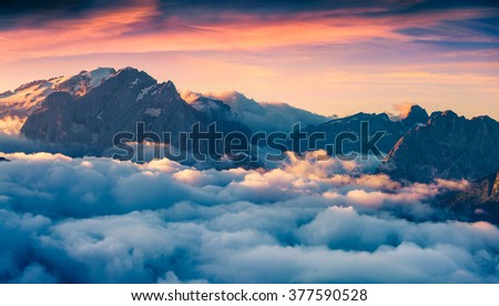 Foggy morning scene in the Val di Fassa valley. View from the bird's eye from Sella pass, Province of Bolzano - South Tyrol. Sunrise in Dolomite Alps, Italy, Europe. Dramatic summer landscape. - stock photo