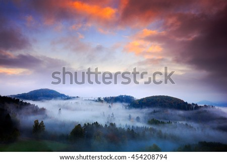 Foggy morning with beautiful orange clouds. Cold misty foggy morning in a fall valley of Bohemian Switzerland park. Hills with fog, landscape of Czech Republic, National Park Ceske Svycarsko - stock photo
