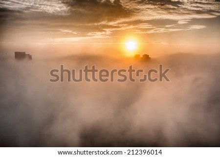 Foggy Morning With Buildings. A city blanketed in fog with the tops of buildings poking through it. - stock photo