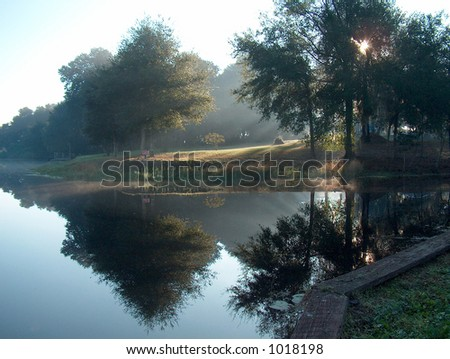 Foggy morning with sun rays shining through. The water was like glass this morning - stock photo