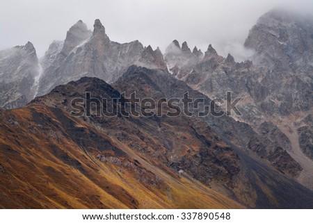 Foggy mountain peaks in Caucasus Mountains near Mt. Ushba. Georgia, Europe, Upper Svaneti, Mazeri, Major Caucasus Range. - stock photo
