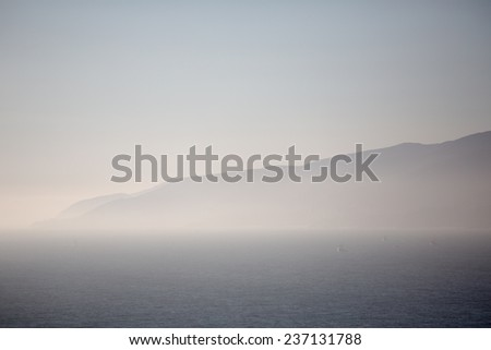 Foggy  mountains next to an ocean - stock photo