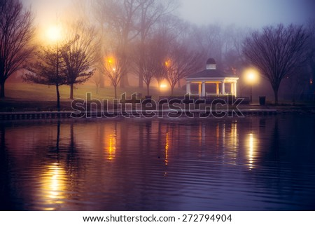 Foggy night scene at pond with lights and gazebo - stock photo