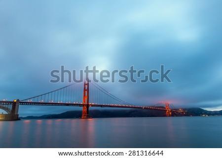 Foggy over Golden Gate Bridge during twilight time. - stock photo