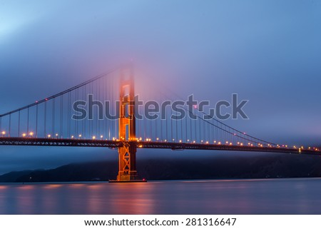 Foggy over Golden Gate Bridge during twilight time.