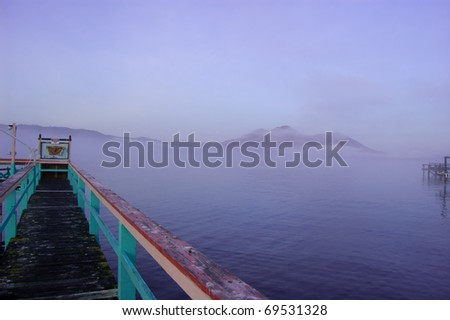 Foggy pier overlooking lake