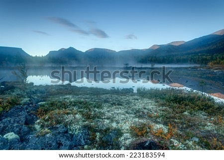 Foggy Polygonal lake with rocks and moss hummock in the foreground in Hibiny mountains in the early morning before sunrise - stock photo