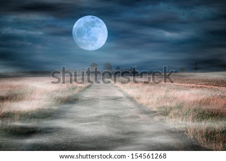 Foggy road to the moon - stock photo