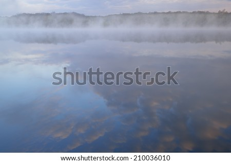 Foggy, spring shoreline of Deep Lake at dawn, Yankee Springs State Park, Michigan, USA  - stock photo
