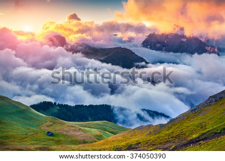 Foggy summer scene in the Val di Fassa valley with Sella pass (Passo Sella) between the provinces of Trentino and South Tyrol, Italy, Europe. Sunrise in Dolomite Alps. - stock photo