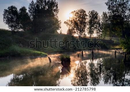 Foggy sunrise with visible sun-rays - stock photo