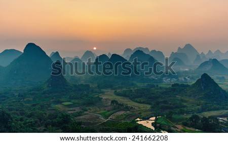 Foggy sunset. The view from the top of the Vine Mountains near Guilin - China - stock photo