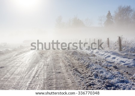 Foggy winter road near a rural farm