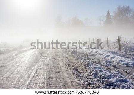 Foggy winter road near a rural farm - stock photo