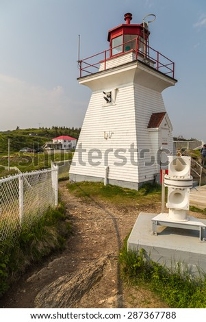 Foghorn in foreground of vertical image of historic Cape Enrage Lighthouse and Tourist Complex.