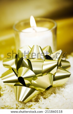Foil bow on imitation snow with candle in the background.  - stock photo