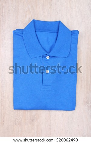 Fold blue polo shirt on wooden background