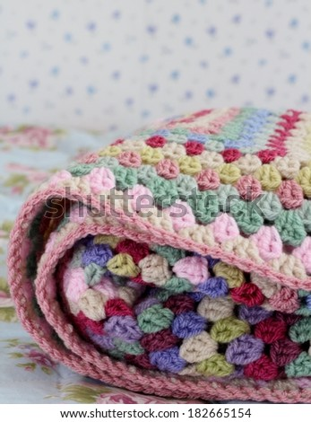 Folded crochet afghan blanket in shabby chic bedroom, granny stitch in yarn of pink, cream, pink, purple and cream  - stock photo
