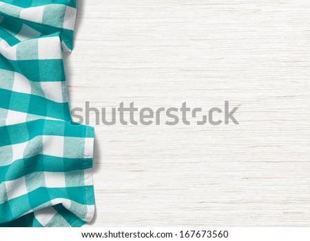 folded cyan tablecloth on bleached wooden table - stock photo