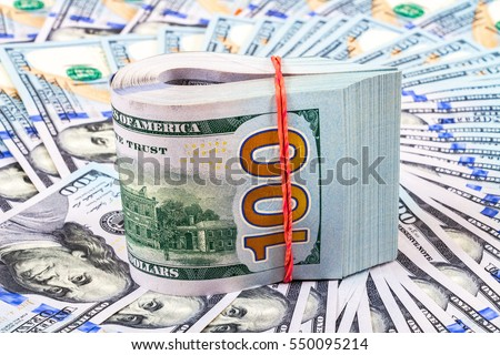 Folded dollar bills wrapped by rubber band over dollars banknotes