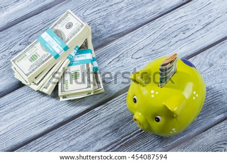 Folded dollars in money box. Piggy bank near money bundles. Don't waste all money. Small savings for the vacation. - stock photo
