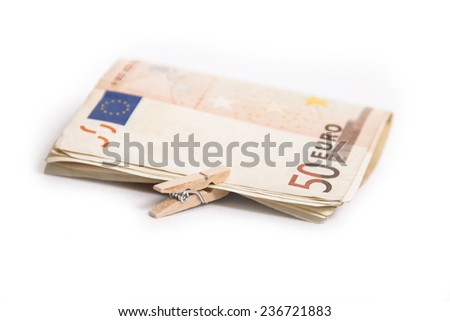 Folded euro banknotes clipped with wooden peg on a white background.