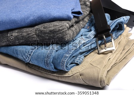 Folded jeans, shirts and sweaters with a belt - stock photo
