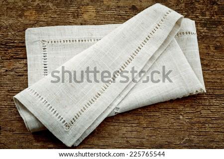 folded linen napkin on old wooden table - stock photo