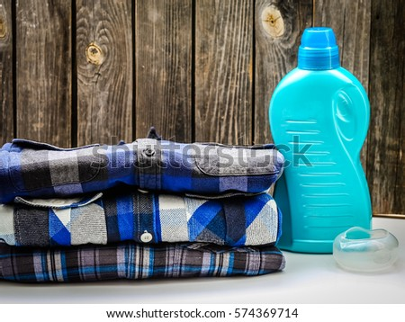 folded men's shirt in the box and washing powder on wooden background ,concept of purity and fashion