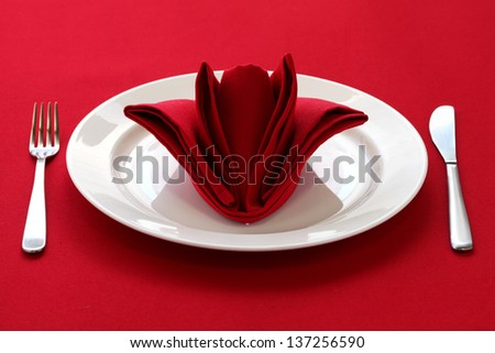 folded napkin like a rose bud, table setting on red background - stock photo