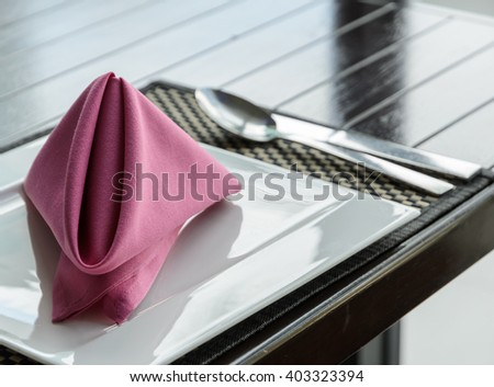 Folded napkin on white plate, table setting in retro filtered effect image - stock photo