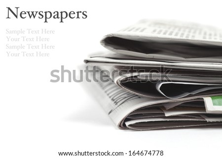 Folded newspapers on white background with copy space and easy to remove sample text. Macro image with shallow depth of focus - stock photo
