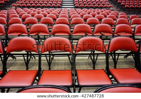 Folded red chairs at a multipurpose arena and sports stadium
