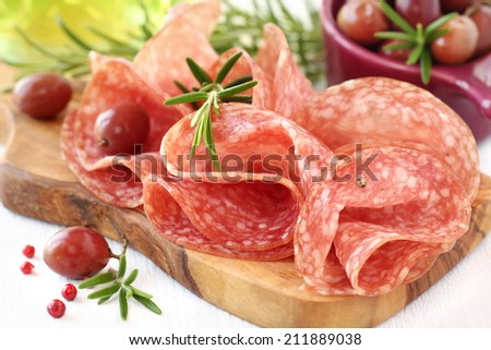Folded salami on a wooden cutting board with fresh rosemary sprigs and olives - stock photo