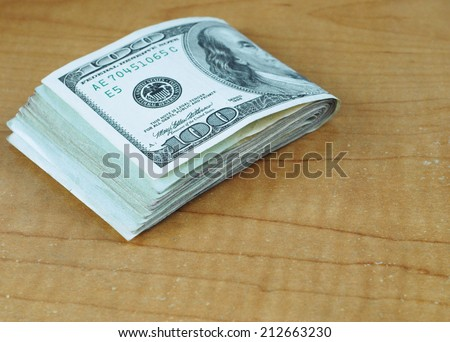 Folded stack of many US one hundred dollar bills with likeness of Ben Franklin on scratched and worn desk with copy space. Good for any fiscal, finance, currency, market, investment or budget concept - stock photo