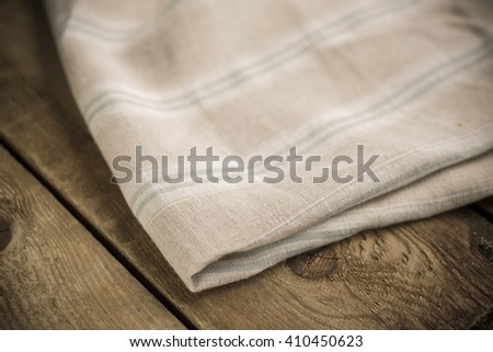 Folded white, beige and faint blue striped cotton fabric or linen on wooden surface.
