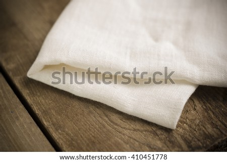 Folded white cotton fabric or linen on wooden surface.